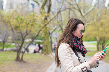 Young woman with a phone in the park outdoors
