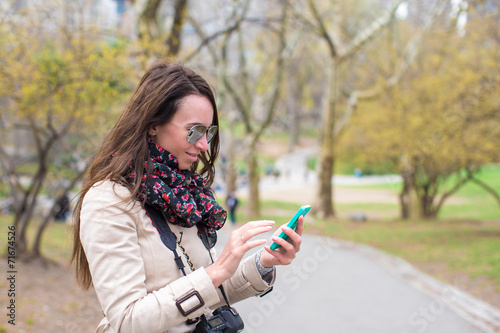 Young girl with a phone in the park - 71674526