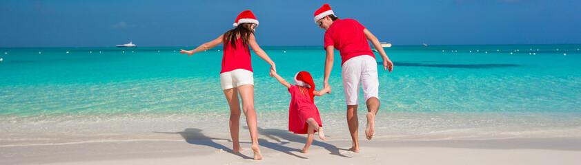 Happy family in Christmas Hats having fun on white beach