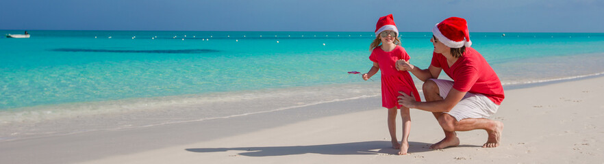 Little girl and happy dad in Santa Hat at exotic beach