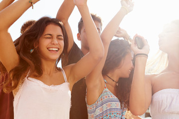 Group Of Teenage Friends Dancing Outdoors Against Sun
