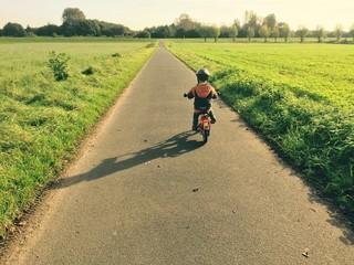 Kind fährt Fahrrad draußen