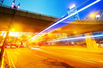 traffic light trails in modern business city under pedestrian br