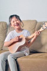 Asian little girl hold an ukulele and smiling