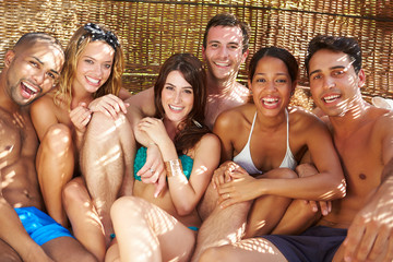 Group Of Friends In Swimwear Relaxing Outdoors Together