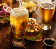 canvas print picture - beer being poured into glass with gourmet hamburgers