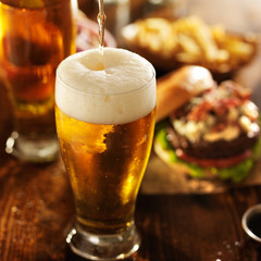 ice cold beer pouring into glass with burgers