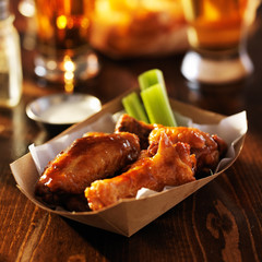 basket of barbecue buffalo chicken wings with celery sticks
