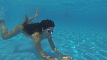 Amazing slim girl in a white bikini swimming under water