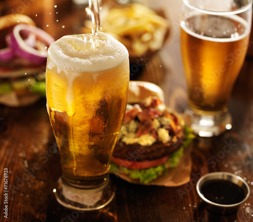 Foto op Canvas Bier / Cider beer being poured into glass with gourmet hamburgers