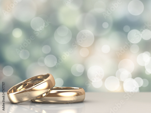 Leinwanddruck Bild A pair of gold wedding rings with bokeh background