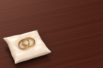 A pair of gold wedding rings on top of a pillow
