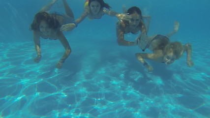 Beautiful girls in bikini swimming underwater