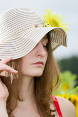 Young girl in a hat with a sunflower