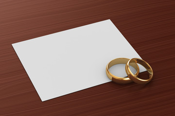 A pair of gold wedding rings and a card