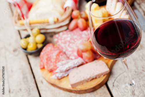 Fotobehang Vlees Glass of red wine with charcuterie assortment on the background
