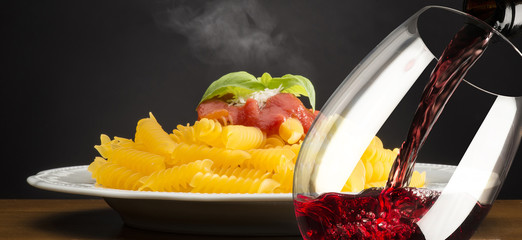 dish with macaroni and glass of red wine