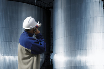 oil worker pointing at ginat fuel storage towers, tanks