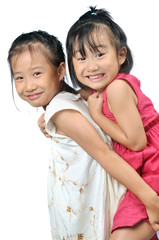 Asian little girl carries her sister on her back