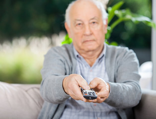 Senior Man Using Remote Control While Sitting On Couch