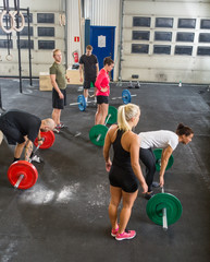 Trainers With Athletes Lifting Barbells