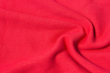 Texture of bright, acid rad cloth with pleats