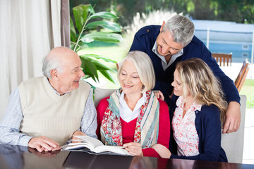 Happy Couple With Grandparents Reading Book In Nursing Home