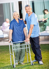 Happy Caretaker Helping Senior Woman To Use Zimmer Frame