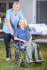Male Nurse Standing With Senior Woman On Wheelchair