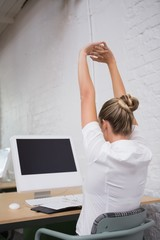 Businesswoman stretching hands in front of computer