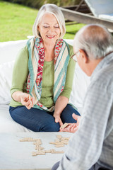 Senior Woman Playing Dominoes With Man