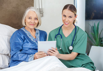 Smiling Senior Woman And Caretaker Holding Tablet PC