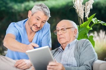 Male Nurse Showing Something To Senior Man On Digital Tablet
