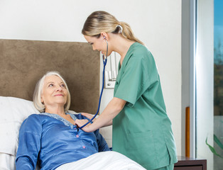 Caretaker Examining Senior Woman At Nursing Home