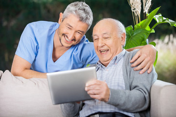 Male Nurse And Senior Man Laughing While Looking At Digital PC