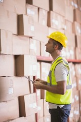 Warehouse worker using digital tablet in warehouse