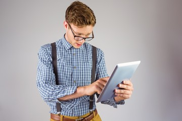 Geeky businessman using his tablet pc
