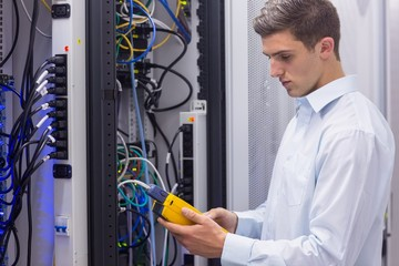 Focused technician using digital cable analyser on servers
