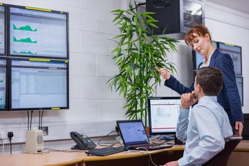 Focused colleagues analyzing result on their computer