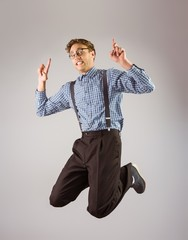 Geeky hipster jumping and pointing