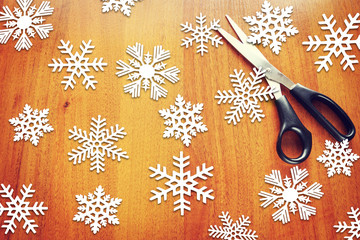 New Year background with paper snowflakes on wooden surface