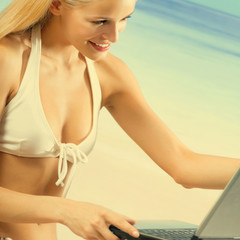 Woman in bikini with laptop on beach
