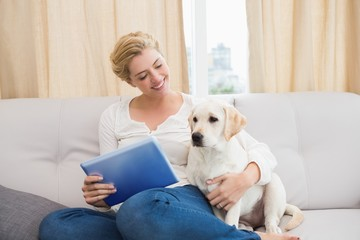 Happy blonde using tablet pc with puppy
