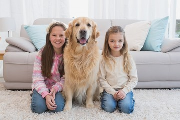 Sisters sitting on rug with golden retriever smiling at camera
