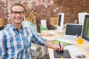 Happy male photo editor using computer in office