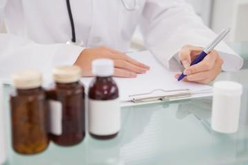 Vet writing on clipboard the prescriptions