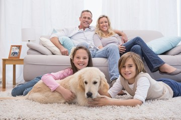 Cute siblings playing with dog with their parent on the sofa
