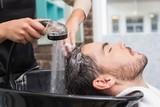 Fototapety Hair stylist washing mans hair