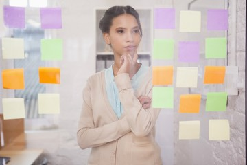 Creative businesswoman looking at sticky notes on window