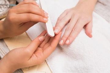 Nail technician giving customer a manicure